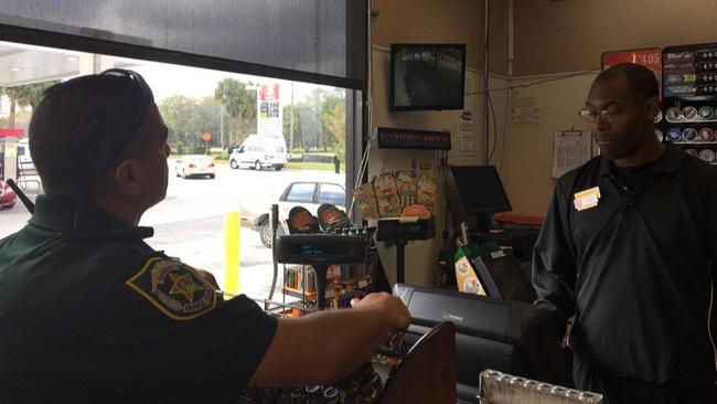 An Orange County Sheriff's Office deputy checks security footage from a neighboring business.