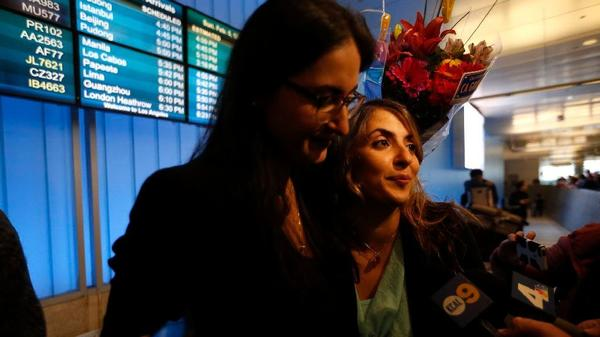 California student Sara Yarjani, right, is greeted by sister Sahar Muranovic at LAX on Sunday. Yarjani, who was born in Iran and lives in Austria, was detained at the airport and deported last week. (Genaro Molina / Los Angeles Times)