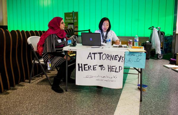 Volunteer translator Nour Our, left, and volunteer attorney Kat Choi offer help to travelers as they arrive at Los Angeles International Airport. (Kyle Grillot / AFP/Getty Images)