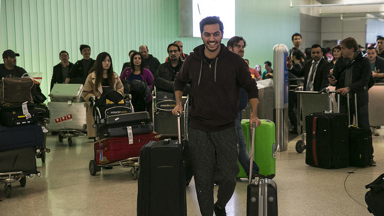 Abdullah Al-Rifaie rushes to meet his family at Los Angeles International Airport on Sunday after waiting for several days in Jordan to see if he would be allowed to reenter the U.S. (Robert Gauthier / Los Angeles Times)