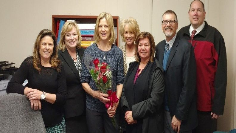 A smiling Food and Nutrition Services Director Kati Harbour is surrounded by district administrators and co-workers congratulating her for her Administrator of the Year honor.