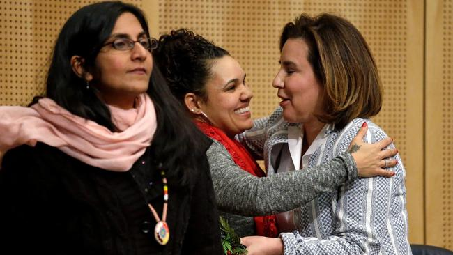 Seattle City Councilwoman Kshama Sawant, left, as fellow Councilwoman Debora Juarez, right, is embraced by Rachel Heaton, a Muckleshoot tribal member, before Wednesday's council meeting.