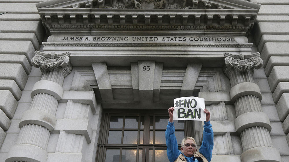 A protester outside the U.S. 9th Circuit Court of Appeals in San Francisco during a hearing over the Trump administration's appeal of a ruling staying the original travel ban. (Jeff Chiu / Associated Press)