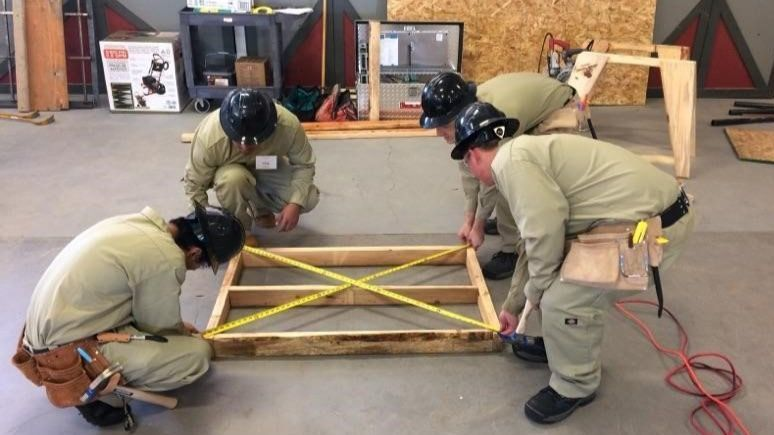 Tony Rincon, Gustavo Mercado, Austyn Wyeth, and Jason Simpson check to be sure the platform they are building during TeamWorks competition is square.