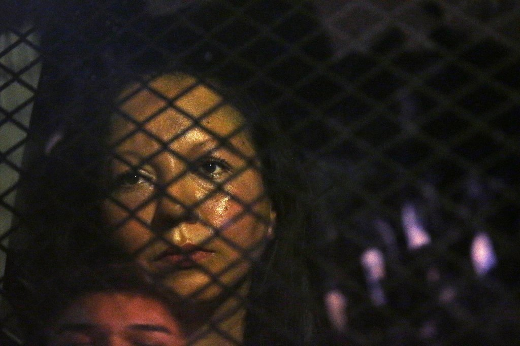 Guadalupe Garcia de Rayos is locked in a van that is stopped in the street by protesters outside the Immigration and Customs Enforcement facility Wednesday, Feb. 8, 2017, in Phoenix.