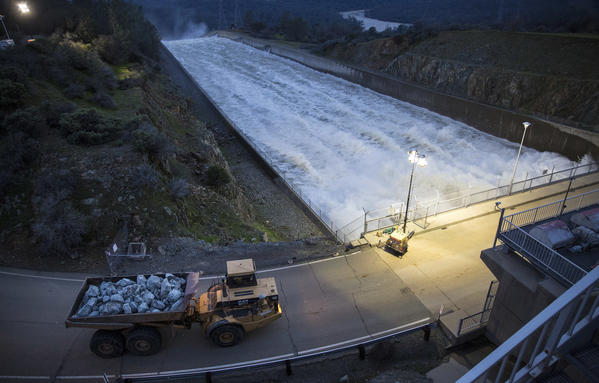 A dump truck crosses the primary spillway on way to deliver boulders to the damaged emergency spillway at Lake Oroville Monday evening (Brian van der Brug / Los Angeles Times)