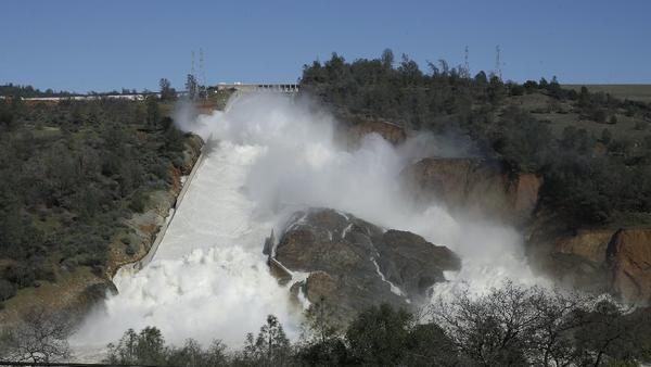 In this Saturday, Feb. 11, 2017, water flows down Oroville Dam's main spillway near Oroville, Calif. Water began flowing over the emergency spillway at the Oroville Dam on Saturday for the first time in its nearly 50-year history after heavy rainfall.