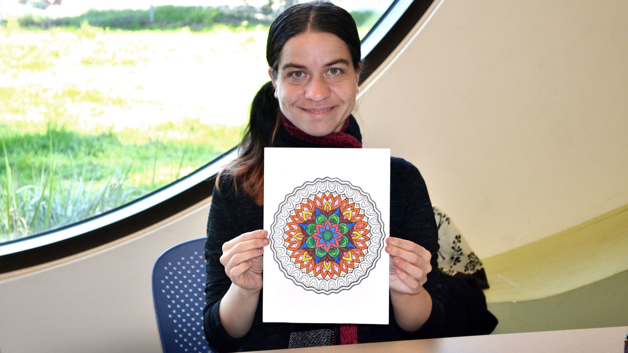 Haeli Greer, who heads up the library's Color Me Calm adult coloring club, shows the mandala she is working on.