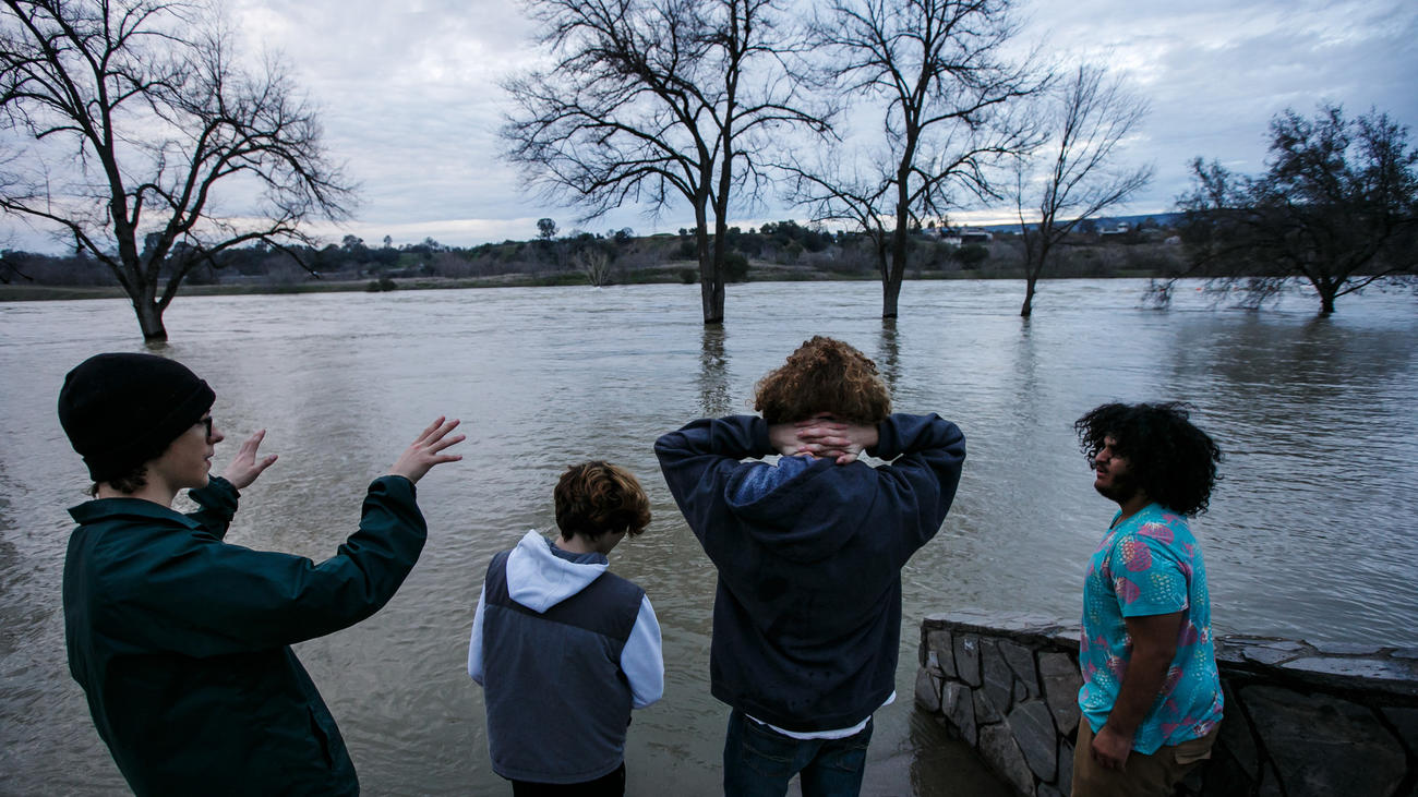 Friends Johnny Eroh, from left, Cody Balmer, Kristien Bravo and Jerel Bruhn hang out by the swollen Feather River in Oroville. (Marcus Yam / Los Angeles Times)