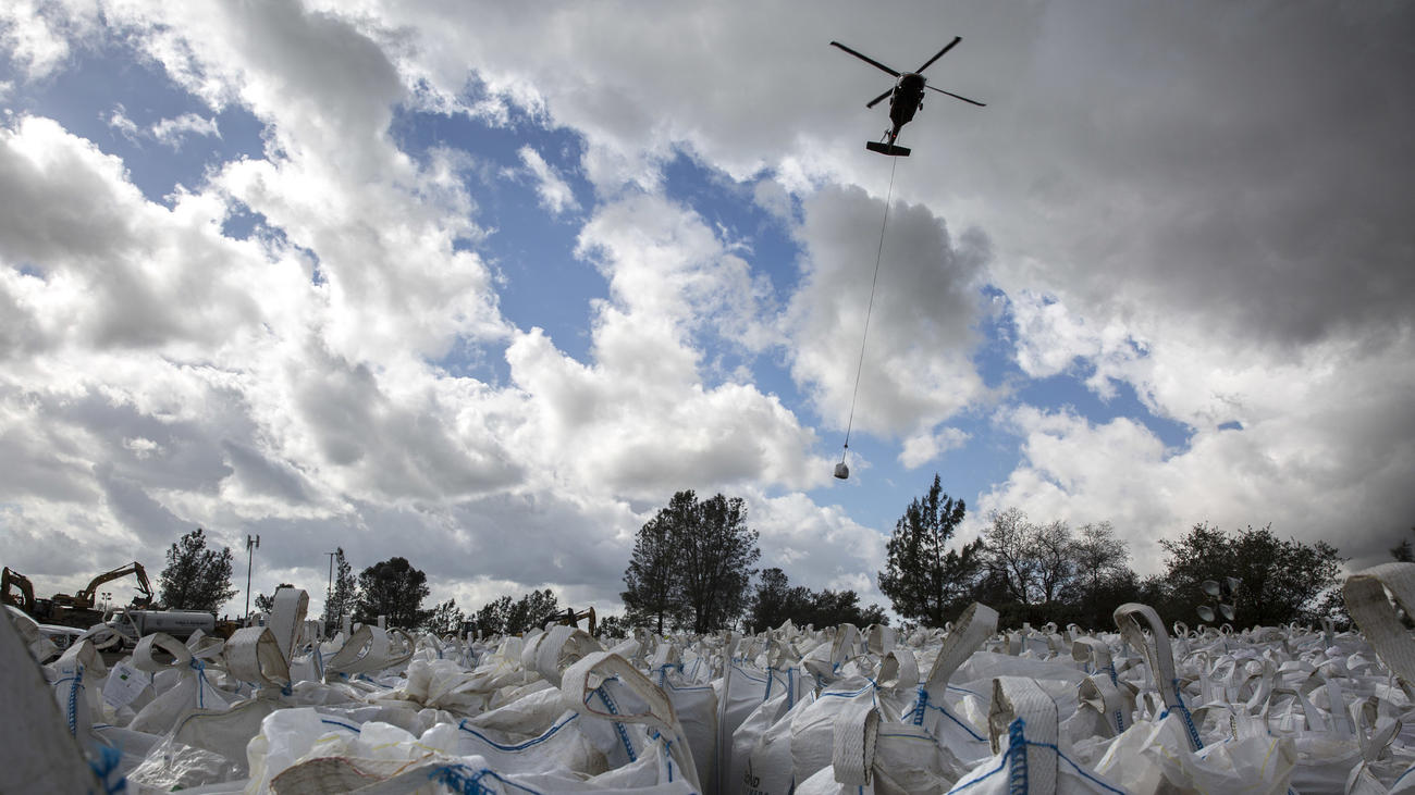 Helicopters ferry sand and rocks from a staging area to the Oroville Dam's emergency spillway repair project. (Brian van der Brug / Los Angeles Times)