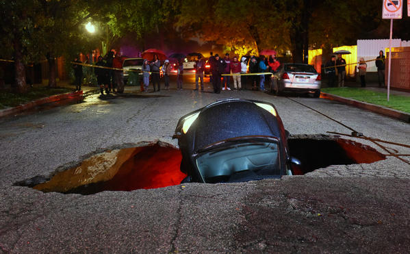 A car sits in a sinkhole on Woodbridge Street near Laurel Canyon Boulevard in Studio City following Friday's rain. (Michael Owen Baker / For The times)