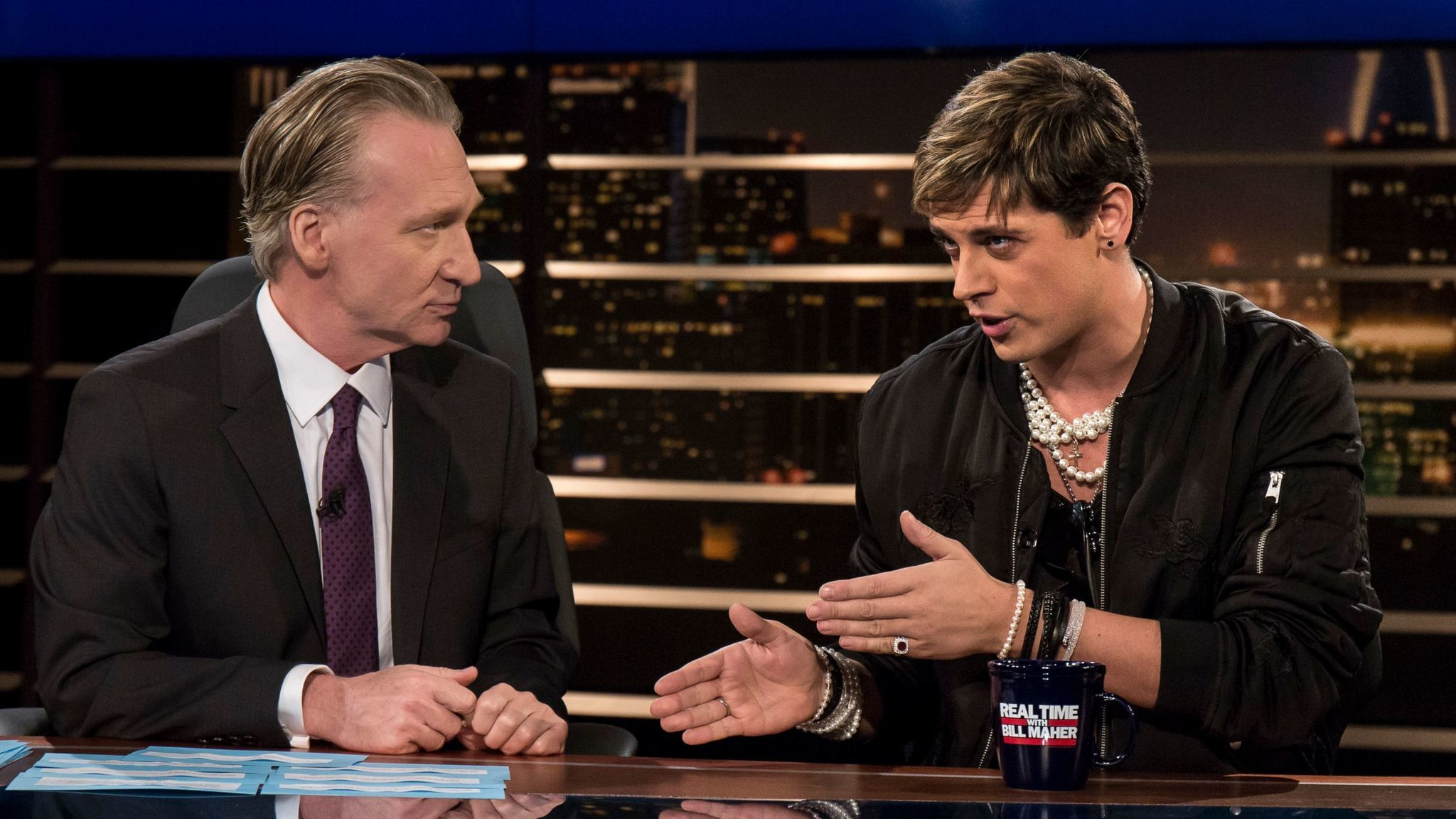 "Bill Maher, left, listens to Milo Yiannopoulos on HBO's ""Real Time With Bill Maher."" (Janet Van Ham / HBO)"