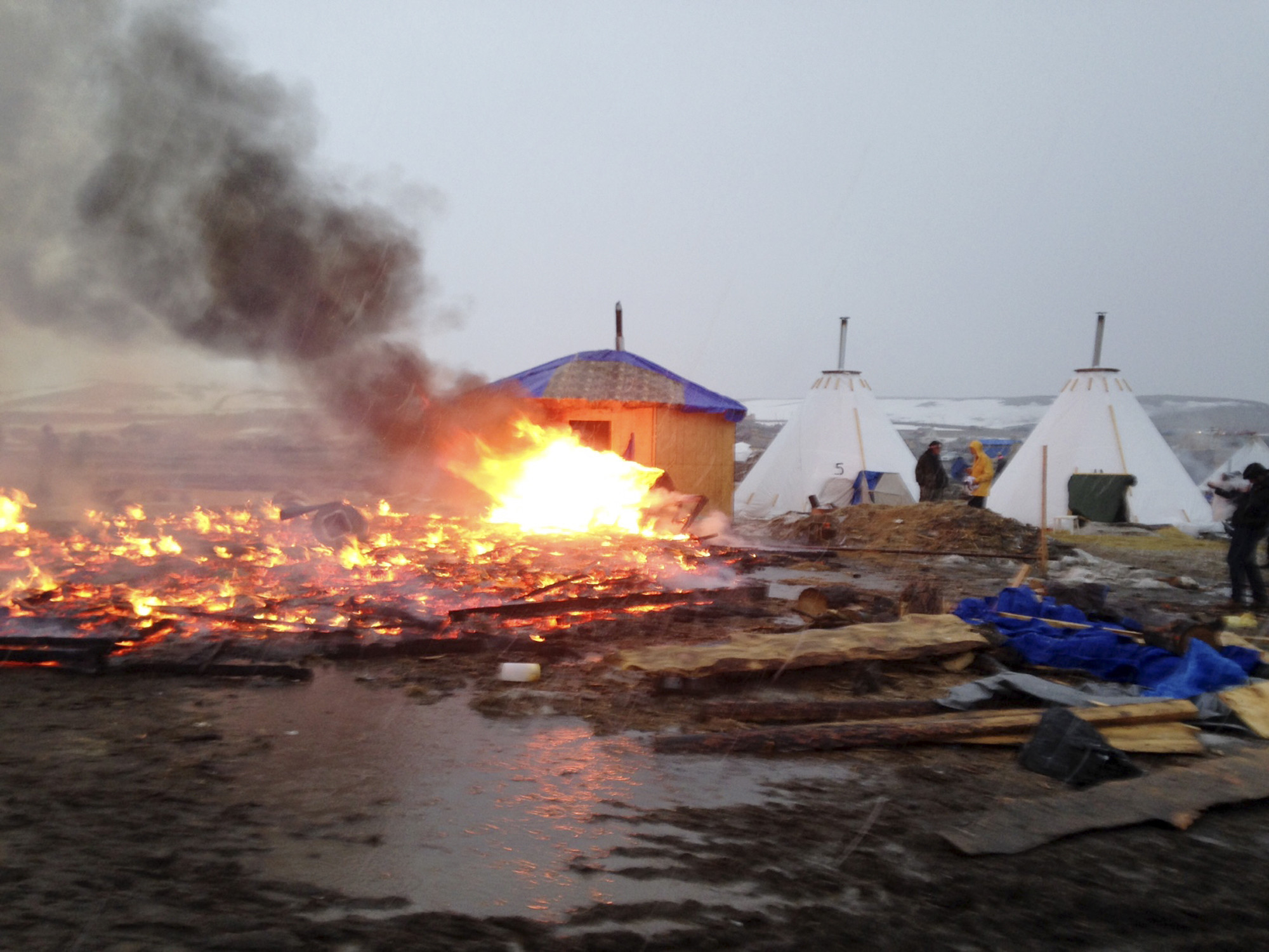 Most Dakota pipeline protesters leave as remnants of camp go up in flames