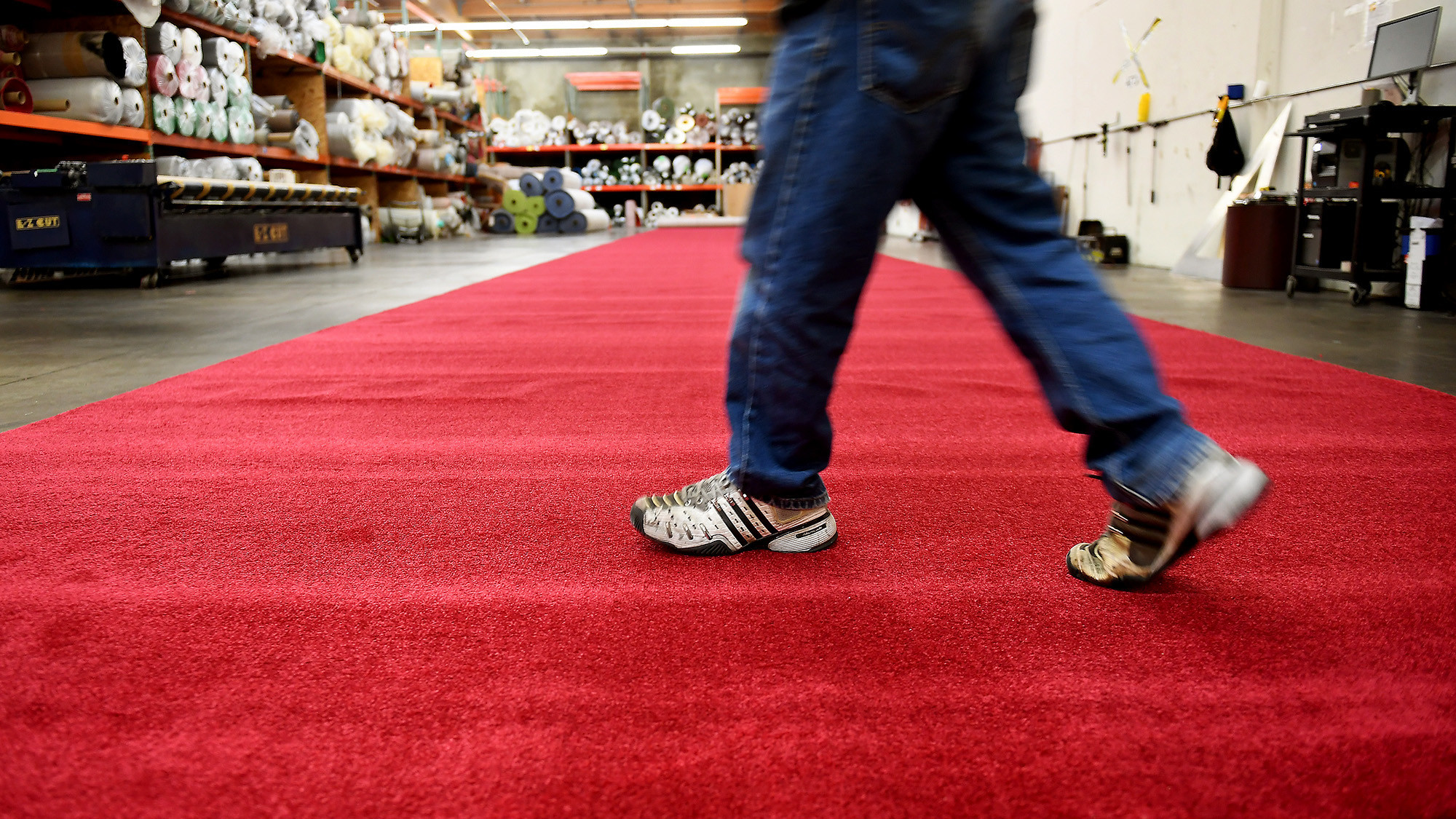 A carpet installer at Signature Systems Group walks across the red carpet in Santa Fe Springs.