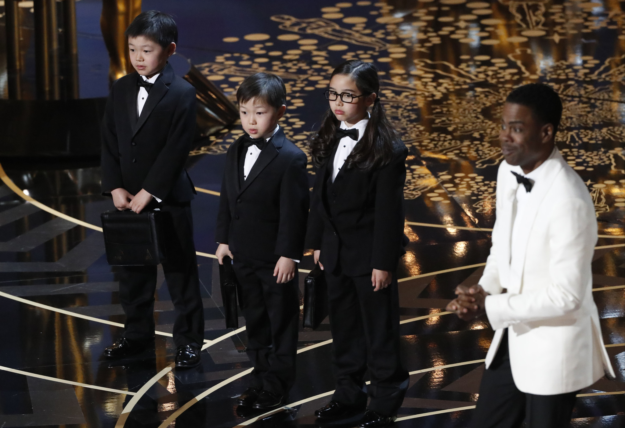 2016 Oscar host Chris Rock, right, introduces children as PriceWaterhouseCopper reps. (Robert Gauthier / Los Angeles Times)