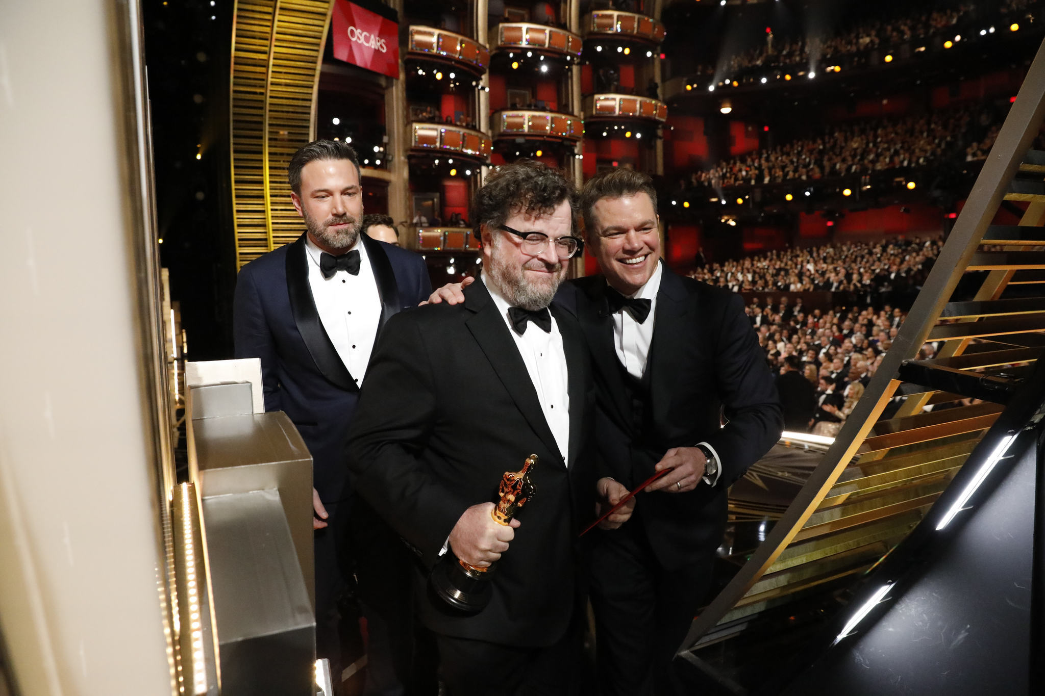 Ben Affleck and Matt Damon lead Kenneth Lonergan offstage upon winning the original screenplay Oscar for 'Manchester by the Sea.' (Al Seib / Los Angeles Times)