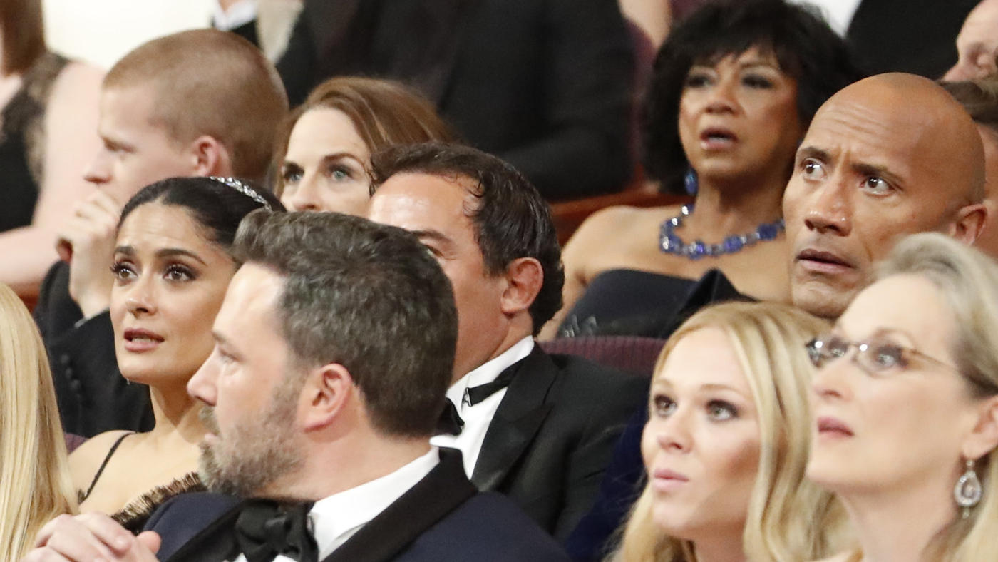 Meryl Streep, right, and Dwayne Johnson react with  arched eyebrows. Sitting behind the Rock is motion picture academy President Cheryl Boone Isaacs. (Al Seib / Los Angeles Times)