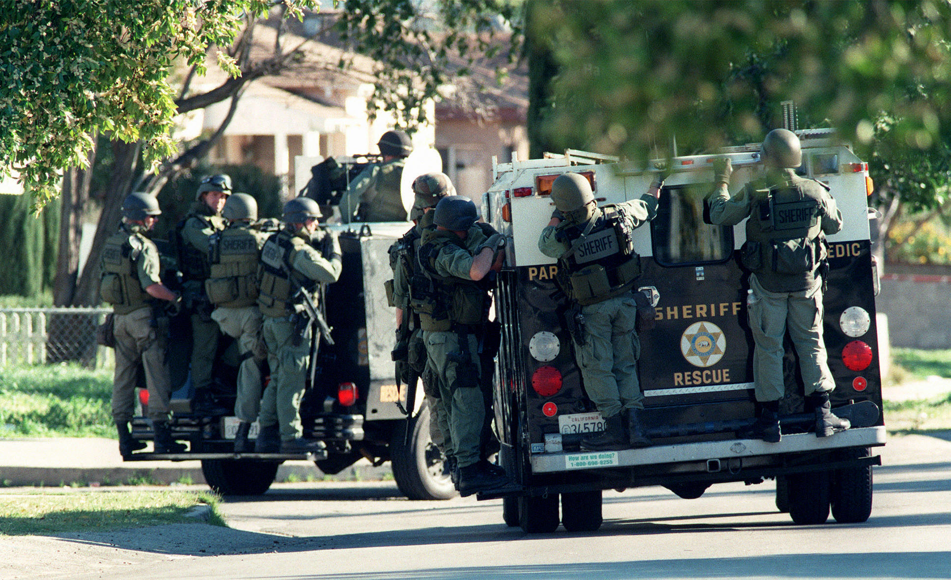 Armored personnel carriers move down Radford Street in a house–by–house search for a suspect.