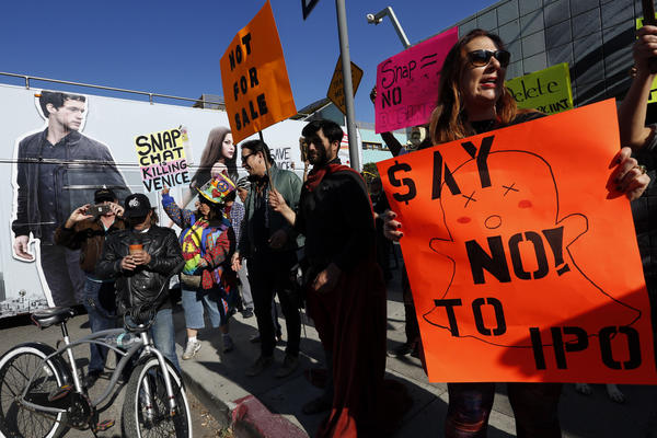 Danielle Mitchell, right, joined fellow Venice residents and business owners to protest in front of Snap offices on Market Street in Venice on Thursday. (Genaro Molina / Los Angeles Times)