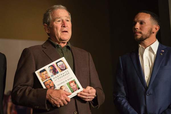 """Former President George W. Bush with Johnnie Yellock, a veteran featured in Bush's new book """"Portraits of Courage,"""" at his presidential library in Dallas on Feb. 28. (Laura Buckman / AFP/Getty Images)"""