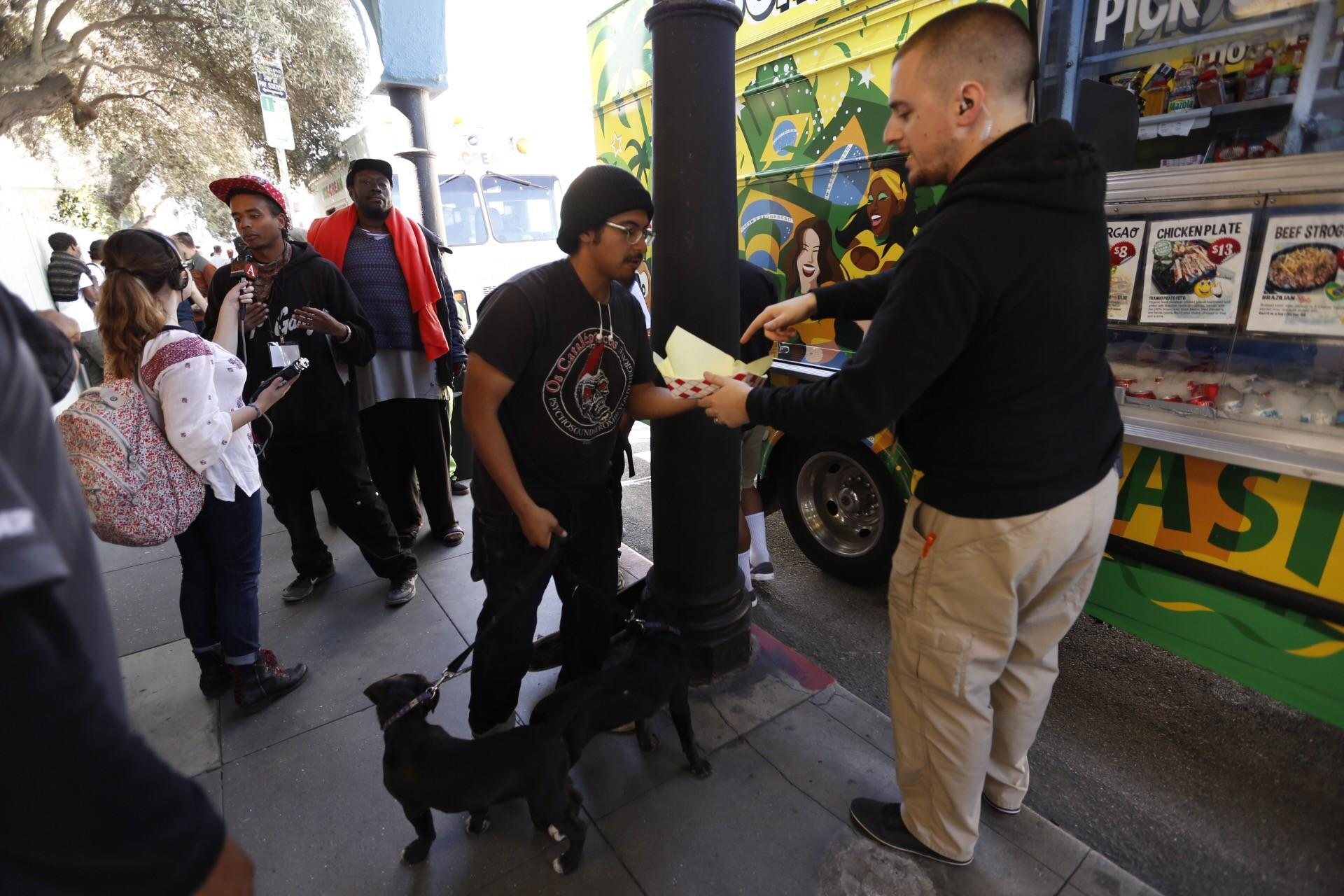 A security guard helps hand out food from a food truck paid for by Snap