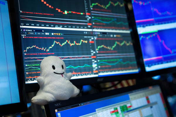 A plush toy of Snapchat's ghost mascot sits on a trader's desk at the New York Stock Exchange. (Drew Angerer/Getty Images)