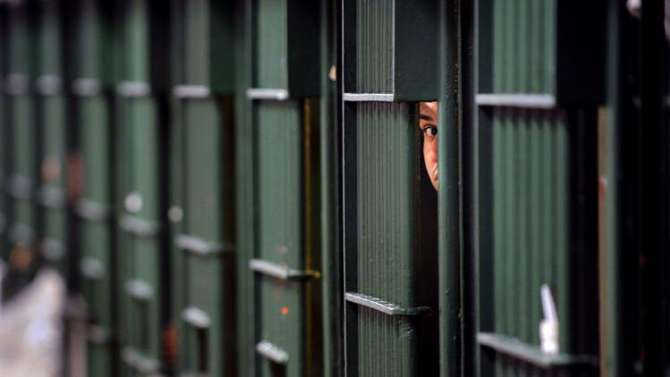 A prisoner peeks through the bars of his cell at the Men's Central Jail in Los Angeles. (Los Angeles Times)