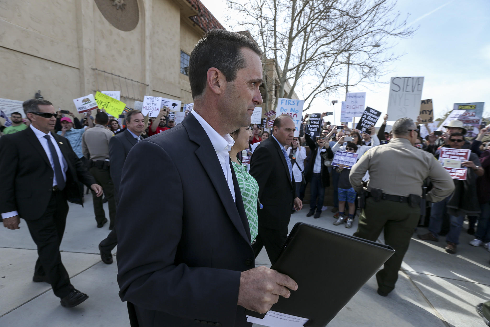 Rep. Steve Knight (R-Lancaster) walks past protesters as he leaves after holding a town hall meeting on Saturday in Palmdale. (Irfan Khan / Los Angeles Times)
