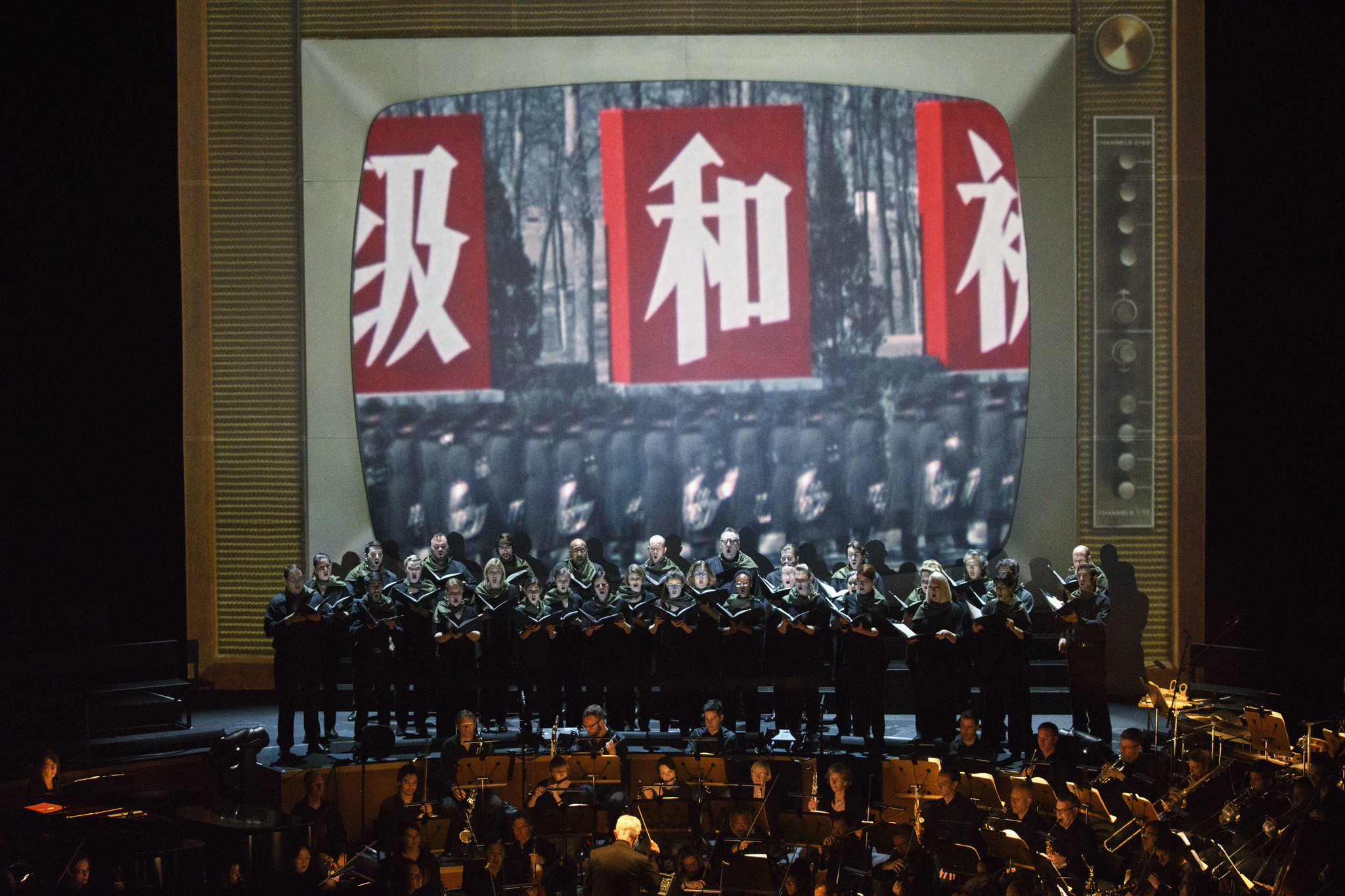 "The L.A. Phil performs with the Los Angeles Master Chorale on the Disney Hall stage, backed by a projection screen made to look like a vintage TV playing historical footage during ""Nixon in China."""
