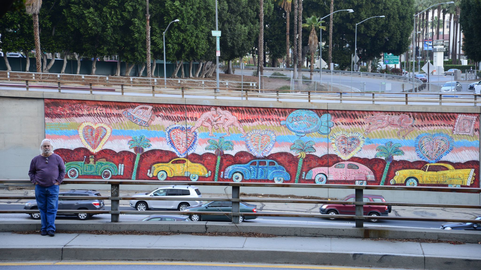 "Frank Romero stands before his mural ""Going to the Olympics"" on the 101 Freeway."