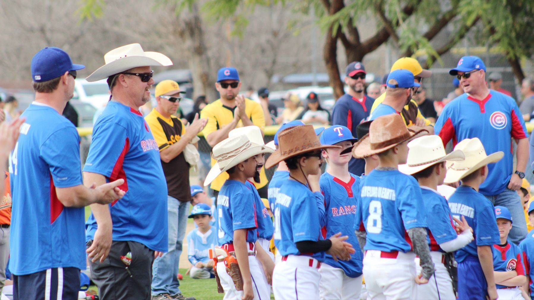 Sporting cowboy hats, Mustang division players make their presence known as the Texas Rangers during opening day ceremonies March 4.
