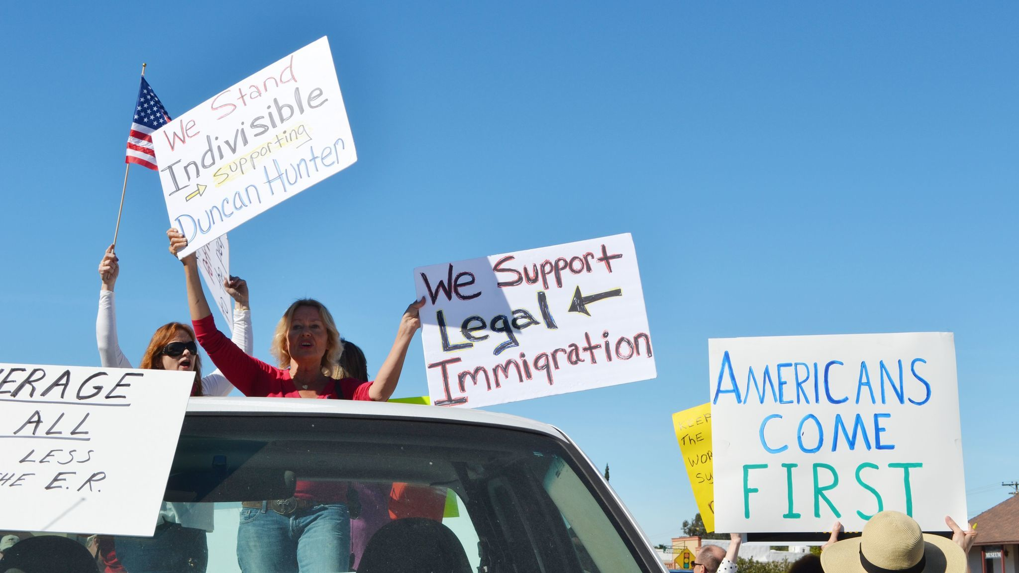 Mary Moran, center, and others show their support for the congressman and for legal immigration from the back of a pickup truck parked in front of Ramona Mainstage.