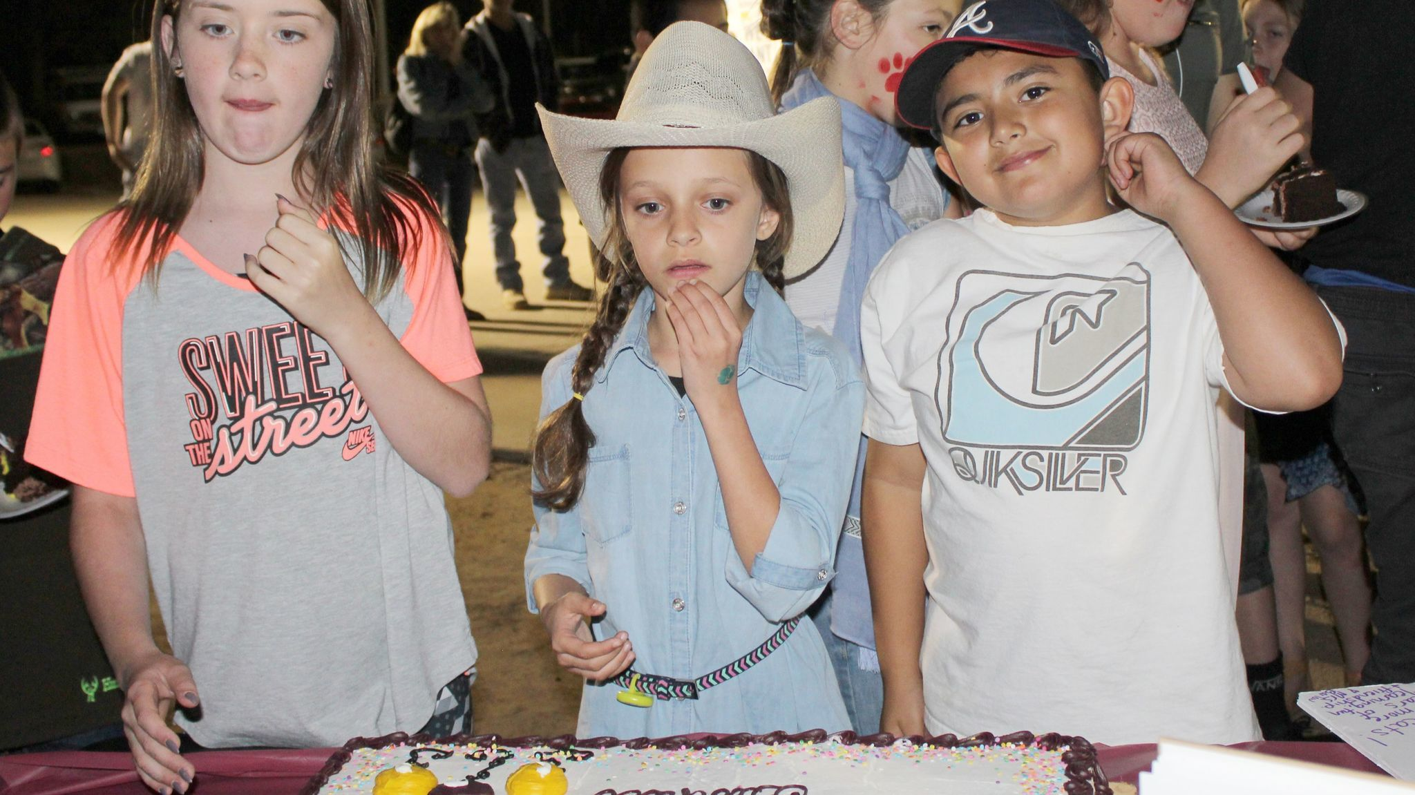 Fourth-graders Josie Harmon, Kayla Del Real, and George Ortega eye one of the Barnett birthday cakes before receiving their piece.