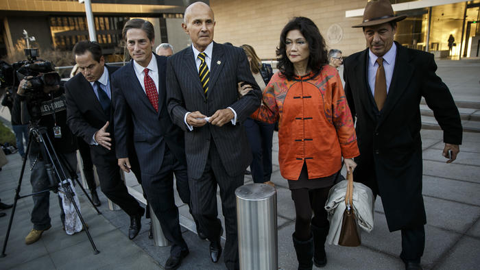 Former Los Angeles County Sheriff Lee Baca, center, escorted by his wife, Carol Chiang, right, and h