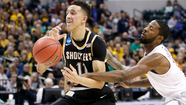 Wichita State guard Landry Shamet is fouled by Dayton guard Scoochie Smith on a drive to the basket during the first half. (Joe Robbins / Getty Images)