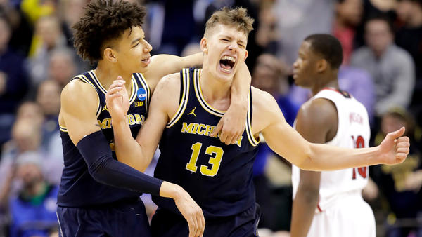 Michigan forward Moe Wagner celebrates with teammate D.J. Wilson after scoring against Louisville in the second half Sunday
