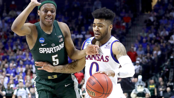 Kansas guard Frank Mason III tries to drive past Michigan State guard Cassius Winston during their second-round game Sunday. (Ronald Martinez / Getty Images)