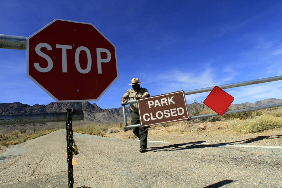 A park official closes the gate to Providence Mountains State Recreation Area in the Mojave Desert. (Irfan Khan / Los Angeles Times)