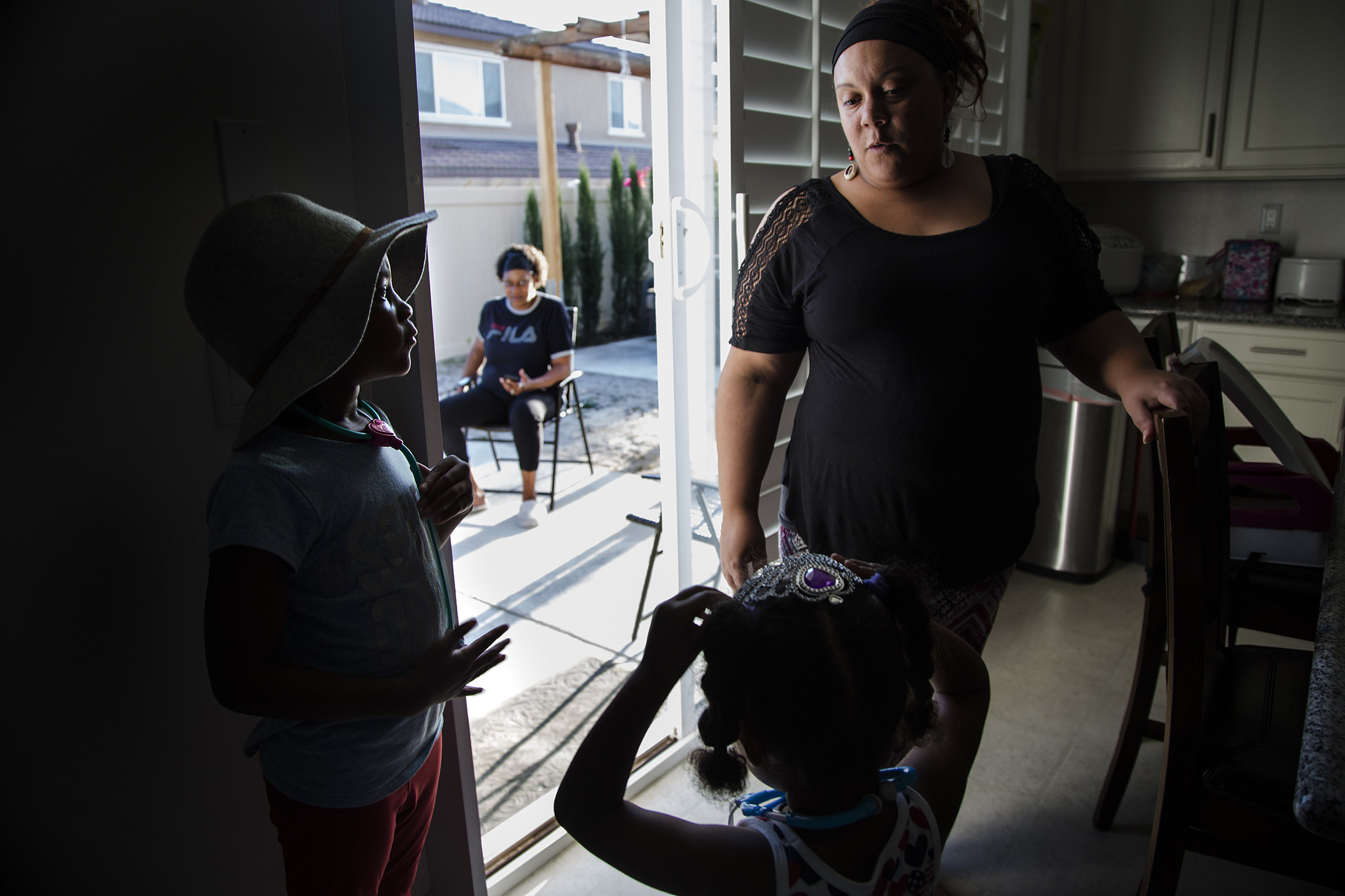Housing manager Erica Wilson, right, spends time with Leana Wilson, 6, left, and Brooklyn Jackson, 3, before dinner at a transitional home in Eastvale that serves former offenders.