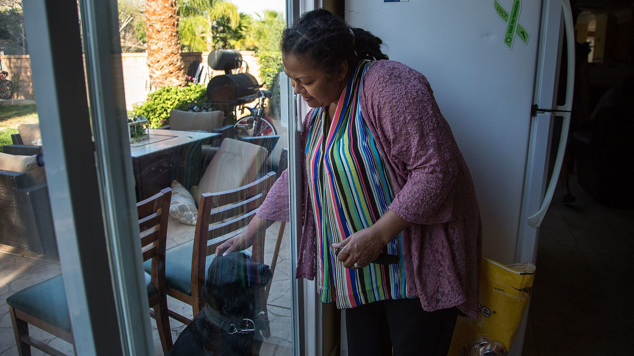 Vonya Quarles, executive director of Starting Over Inc., pets Charlie, a Labrador, at a men's transitional home she runs in Corona. Programs like hers aim to help former inmates reenter society.