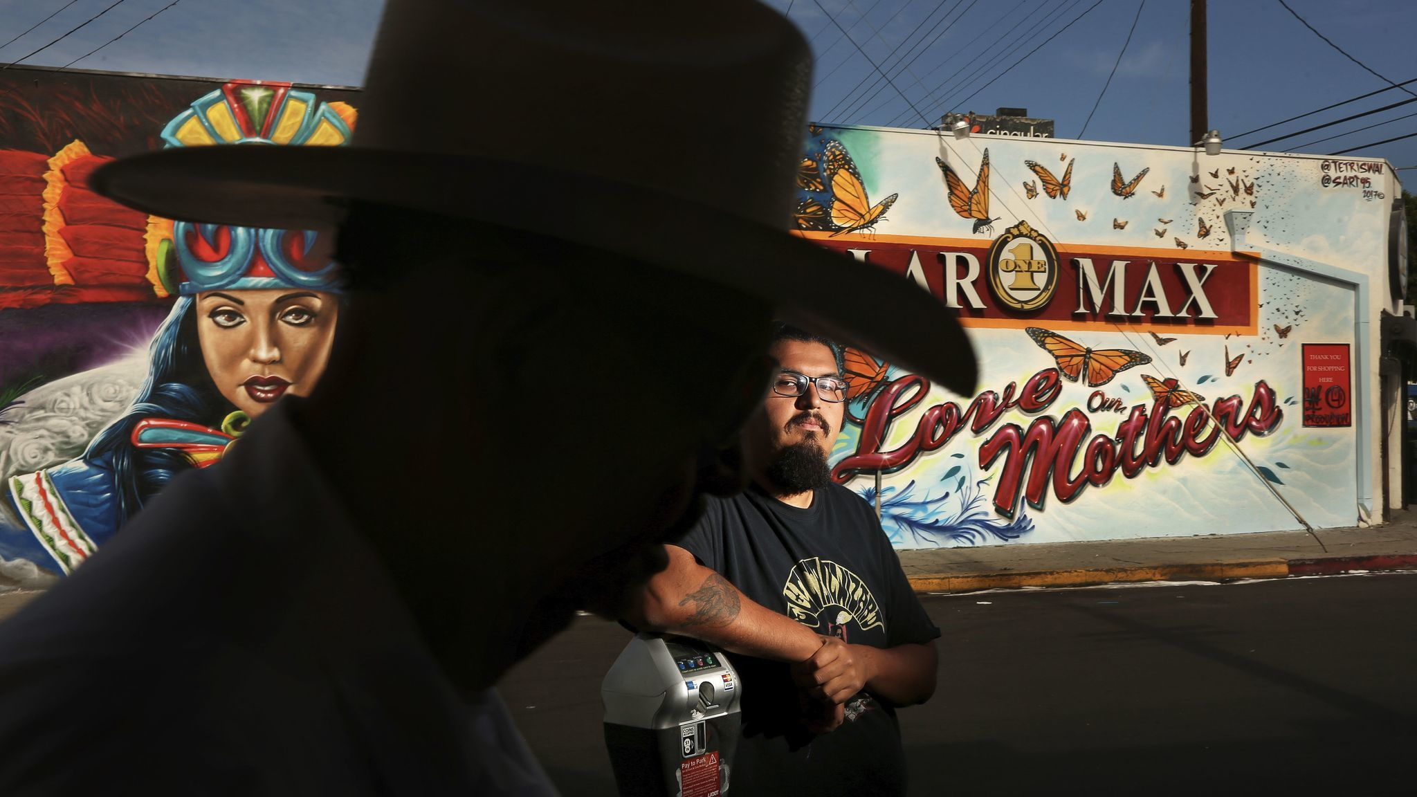 "Adrian Ulloa, 21, stands in front of a mural he worked on that was recently completed on the side of a dollar store that runs along Cesar E. Chavez Avenue in the Boyle Heights. The mural is titled ""Love our Mothers."""