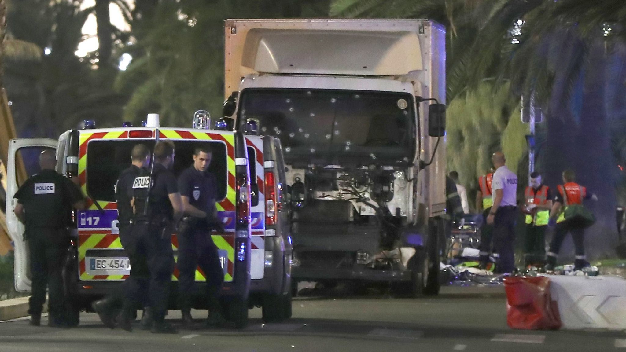 Police officers and rescue workers stand near a truck that plowed into a crowd leaving a fireworks show in the French Riviera town of Nice on July 14, 2016.