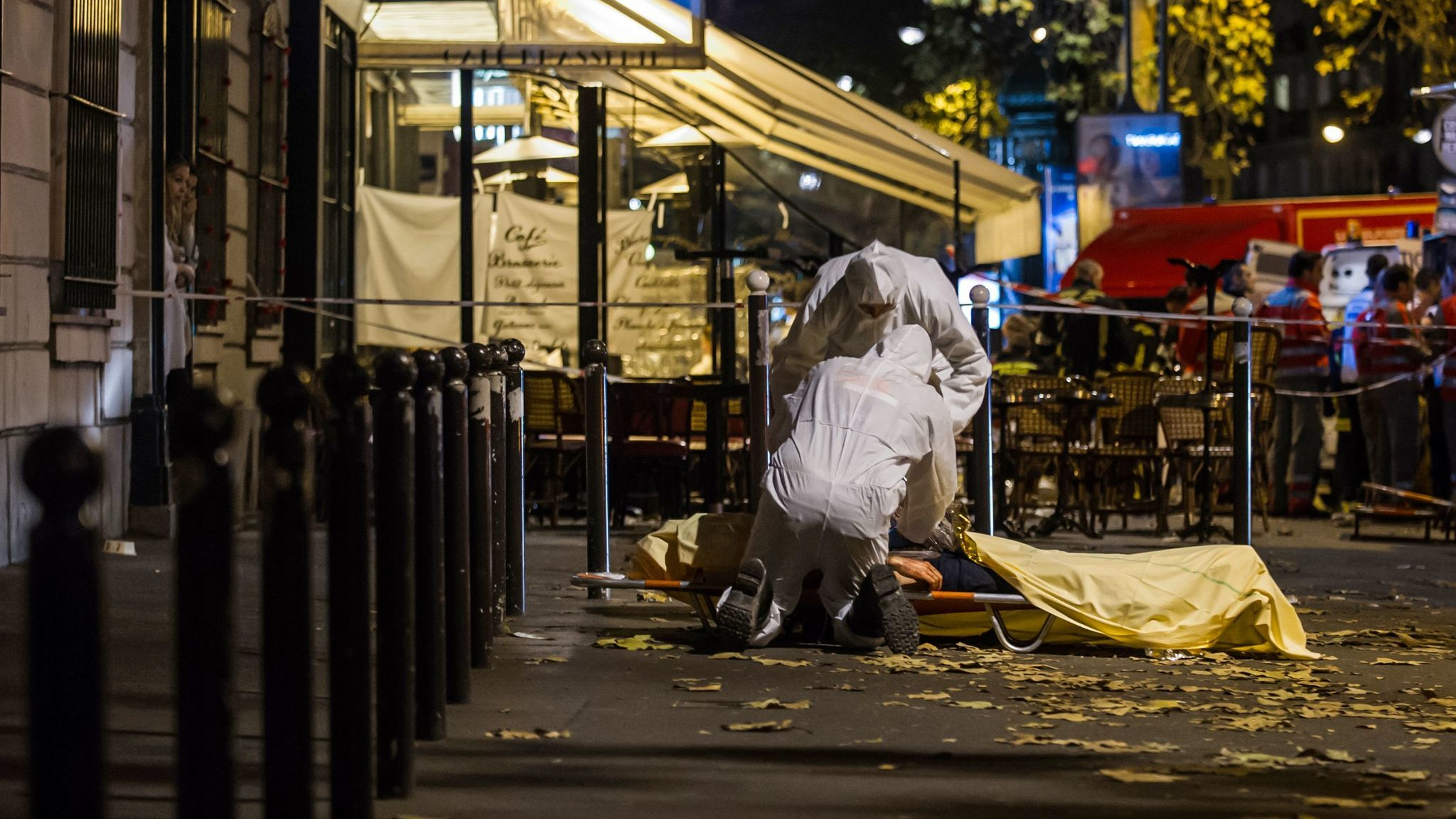 Investigating police officers inspect the lifeless body of a victim of a shooting attack outside the Bataclan concert hall in Paris on Nov. 13, 2015.
