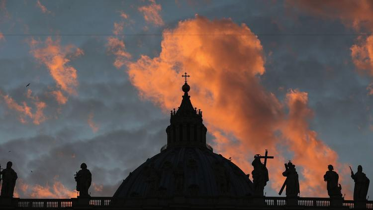 The sun sets over St Peter's Basilica at the Vatican on March 9, 2013.