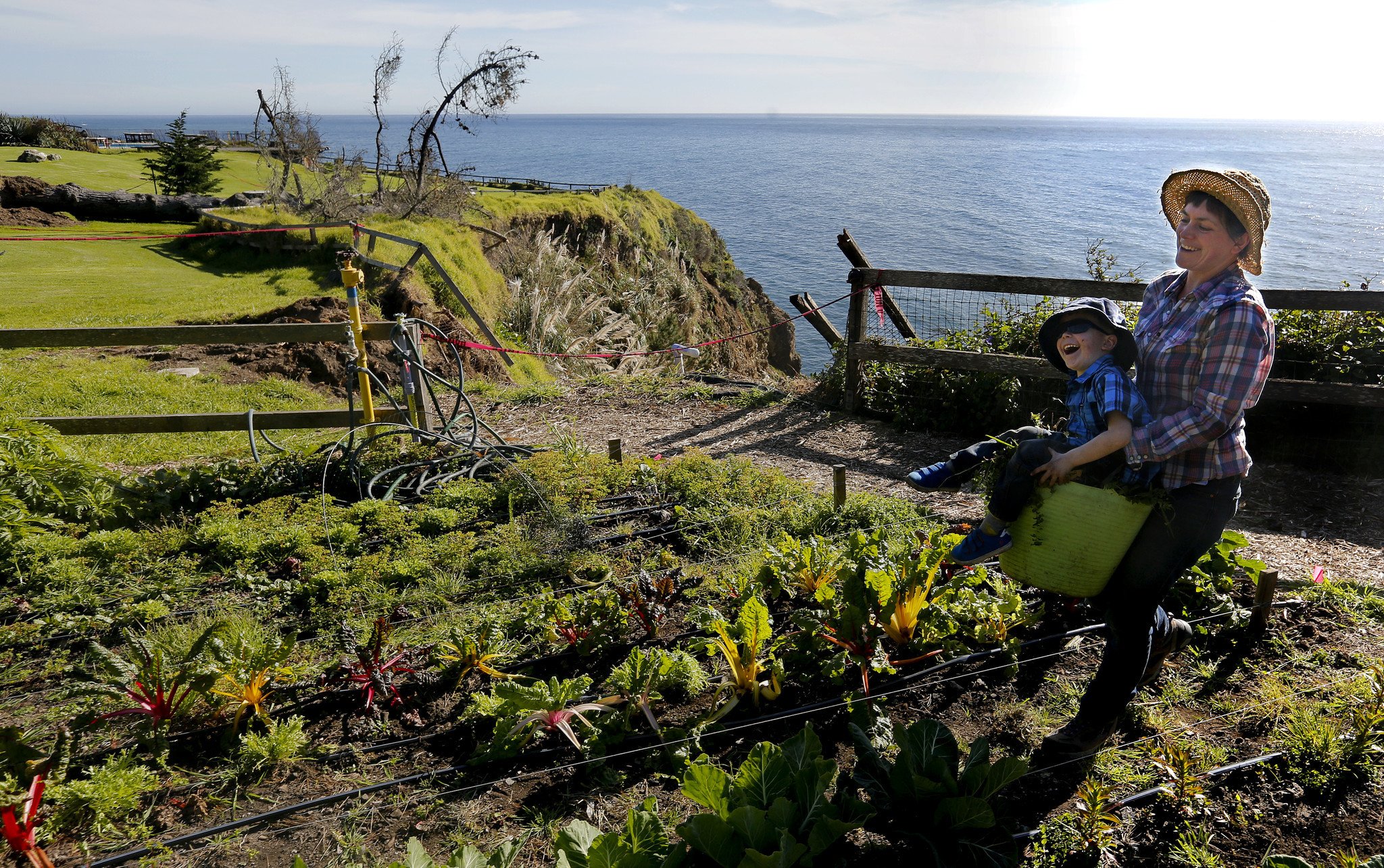 In the absence of visitors to Esalen, Verity Howe, 39, helps tend the center's community garden with her son, Calder, 4. Howe is married to the retreat's gardener.