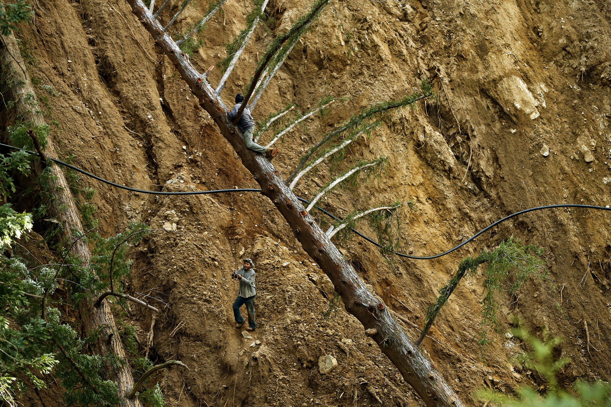 Workers climb a massive slide area above Post Creek near the Ventana Inn in order to replace a water line that had been severed by debris.