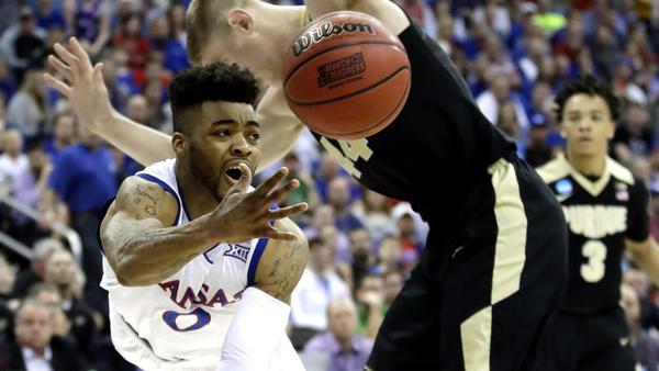 Kansas guard Frank Mason III makes a pass around Purdue center Isaac Haas during the first half Thursday. (Charlie Riedel / Associated Press)