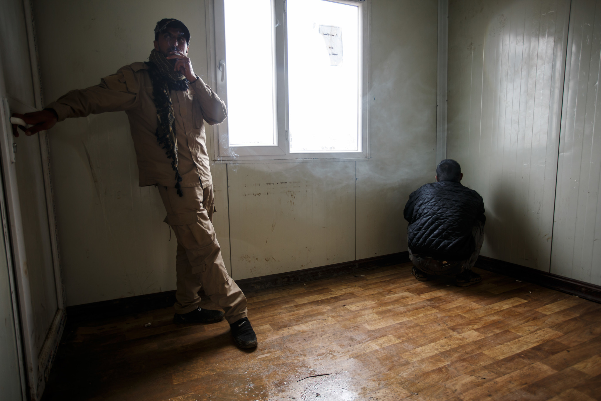 A man suspected of being an ISIS member, right, is put in a holding room before being sent to another facility for further questioning.
