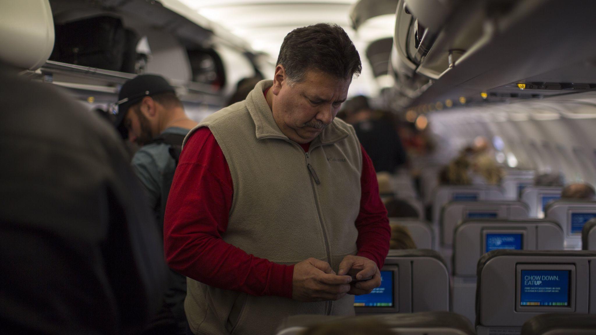 A JetBlue passenger checks his cellphone before disembarking at Long Beach Airport.