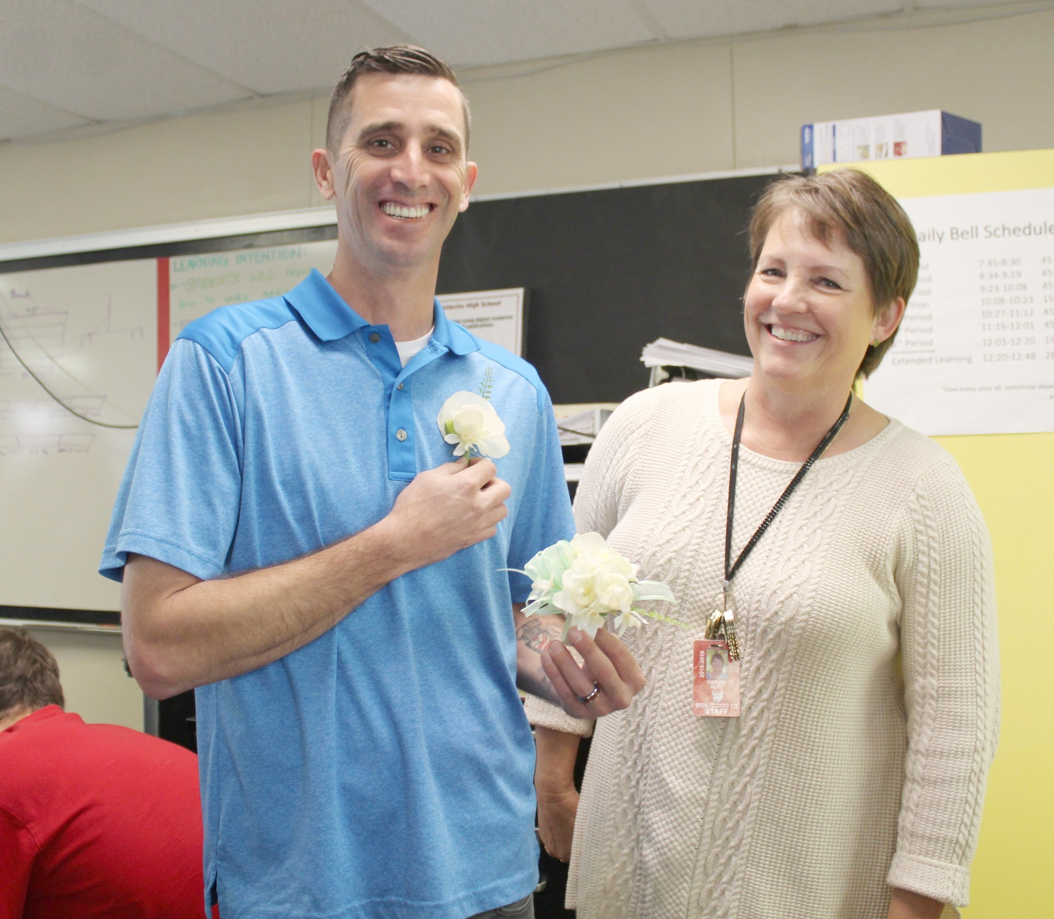 Ramona Unified School District Classified Employee of the Year Caylor Nuth presents Montecito High School construction teacher Nick Jordan  with a boutonniere and corsage she made for him and his daughter to wear at the Father/Daughter Dance at James Dukes Elementary School.